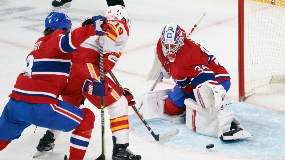 Montreal Canadiens goaltender Jake Allen makes a save on Calgary Flames' Matthew Tkachuk as he is covered by defenceman Ben Chiarot during first period NHL hockey action in Montreal on Friday, April 16, 2021. THE CANADIAN PRESS/Paul Chiasson