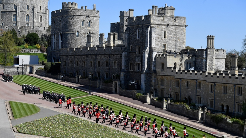 Military personnel in parade dress uniform march past flowers which where placed on the grass for the funeral of Britain's Prince Philip inside Windsor Castle in Windsor, England, Saturday, April 17, 2021. Prince Philip died April 9 at the age of 99 after 73 years of marriage to Britain's Queen Elizabeth II. (Justin Tallis/Pool via AP)