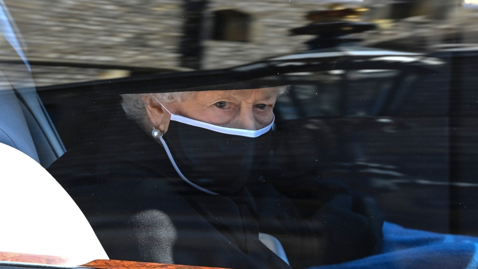 Queen Elizabeth II follows the coffin in a car as it makes it's way past the Round Tower during the funeral of Britain's Prince Philip inside Windsor Castle in Windsor, England Saturday April 17, 2021. (Leon Neal/Pool via AP)