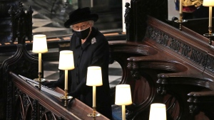 Queen Elizabeth II takes her seat alone in St. George's Chapel during the funeral of Prince Philip, the man who had been by her side for 73 years, at Windsor Castle, Windsor, England, Saturday April 17, 2021. Prince Philip died April 9 at the age of 99 after 73 years of marriage to Queen Elizabeth II. (Yui Mok/Pool via AP)