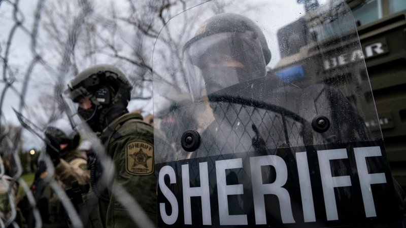 Law enforcement officers guard a perimeter fence as demonstrators gather during a protest over Sunday's fatal shooting of Daunte Wright during a traffic stop, outside the Brooklyn Center Police Department on Wednesday, April 14, 2021, in Brooklyn Center, Minn. (AP Photo/John Minchillo)