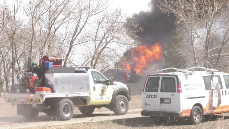 A fire tore through a barn and several other structures on a rural property in Balzac on Saturday.