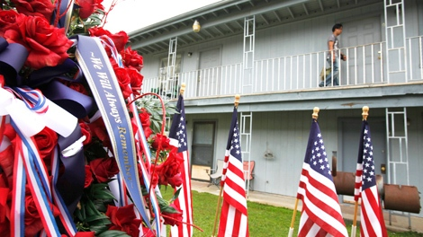 Flags and flowers are shown in front of the apartment, upper right, where Army psychiatrist Maj. Nidal Malik Hasan lived outside of Fort Hood in Killeen, Texas, Monday, Nov. 9, 2009. (AP / Paul Sakuma)