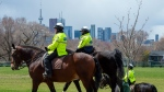 Toronto Police Mounted Unit officers patrol a city park in Toronto on Thursday, April 16, 2020. THE CANADIAN PRESS/Frank Gunn