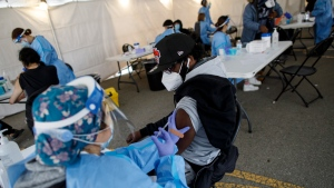 Hamdi Abdulkadir is administered a dose of the Moderna COVID-19 vaccine at a pop-up vaccine clinic in Toronto's Jane and Finch neighbourhood, in the M3N postal code, on Saturday, April 17, 2021. THE CANADIAN PRESS/Cole Burston