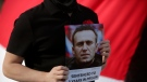 A demonstrator holds a picture of Russian jailed pposition leader Alexei Navalny during a protest demanding freedom for political prisoners, attended by Belarus opposition leader Sviatlana Tsikhanouskaya and organized by a Belorussian cultural association, in Lisbon, Saturday, March 6, 2021. (AP Photo/Armando Franca)