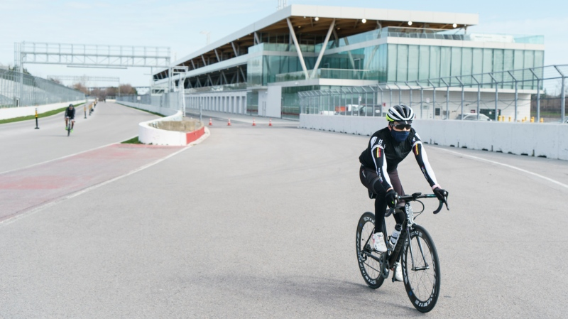 A cyclist rides along the paddocks at Circuit Gilles Villeneuve in Montreal, on Wednesday, April 14, 2021. Governments are evaluating whether or not to approve and fund the Canadian Grand Prix scheduled for June 13 amid the COVID-19 pandemic. THE CANADIAN PRESS/Paul Chiasson