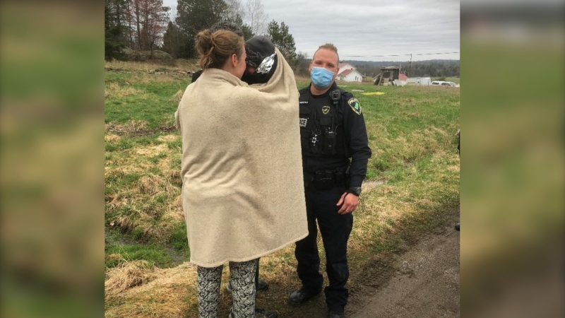 Photo of a missing child being reunited with his mother after being found in the woods in Val-des-Monts, Que. (Photo via MRC des Collines Police / Facebook)