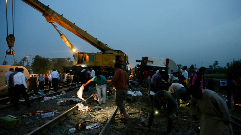 People search for belongings in the aftermath of a passenger train that derailed injuring around 100 people, near Banha, Qalyubia province, Egypt, Sunday, April 18, 2021. The train was travelling to the Nile Delta city of Mansoura from the Egyptian capital, the statement said. (AP Photo/Fadel Dawood)