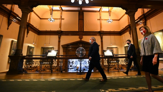 Ontario Premier Doug Ford, left, walks to his press conference at Queen's Park during the COVID-19 pandemic in Toronto on Tuesday, November 3, 2020. The provincial government unveiled a new tiered system for COVID-19 restrictions that will give municipalities and public health units guidelines for when to implement lockdows and closures. THE CANADIAN PRESS/Nathan Denette