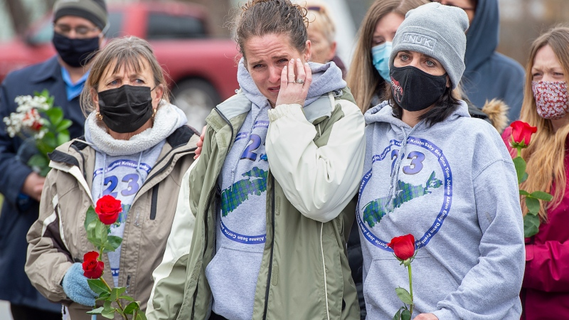 Family and friends of the victims of the April 2020 murder rampage in rural Nova Scotia, stand outside the RCMP detachment as they mark the one-year anniversary in Bible Hill, N.S. on Sunday, April 18, 2021.THE CANADIAN PRESS/Andrew Vaughan