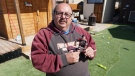 Neil Sasakamoose holding a figurine of his father Fred Sasakamoose. (Francois Biber / CTV News Saskatoon)