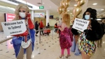 Passengers from New Zealand, at back, are welcomed by drag queens as they arrive at Sydney Airport in Sydney, Australia, Monday, April 19, 2021, as the much-anticipated travel bubble between Australia and New Zealand opens. (AP Photo/Rick Rycroft)