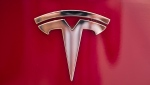 FILE - This Wednesday, Aug. 8, 2018, file photo shows the Tesla emblem on the back end of a Model S in the Tesla showroom in Santa Monica, Calif. (AP Photo/Richard Vogel, File)