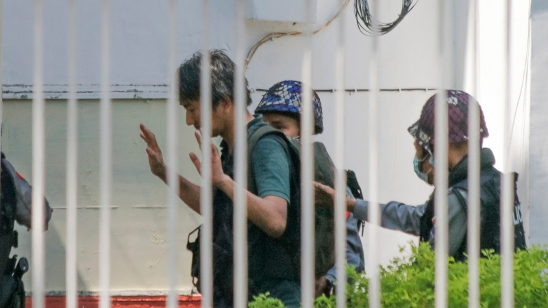 In this Feb. 26, 2021, photo, Japanese journalist Yuki Kitazumi raises his hands as he is escorted by police upon arrival at the Myaynigone police station in Sanchaung township in Yangon, Myanmar. (AP Photo)