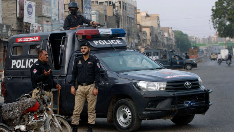 Police officers stand guard at a deserted road due to strikes called by the the country's religious political parties over the security forces's crackdown against a banned Tehreek-e-Labaik Pakistan party, in Karachi, Pakistan, Monday, April 19, 2021. (AP Photo/Fareed Khan)