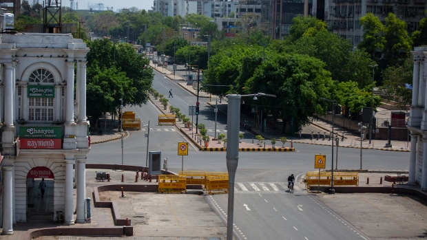 A cyclist pedals past a deserted street during a weekend lockdown in New Delhi, India, Saturday, April 17, 2021. (AP Photo/Altaf Qadri)
