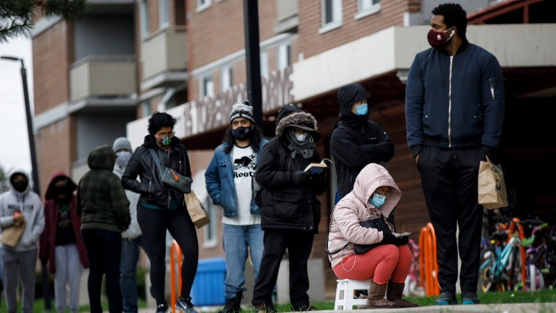 Residents of Toronto's Jane and Finch neighbourhood, in the M3N postal code, line up at a pop-up COVID-19 vaccine clinic on Saturday, April 17, 2021. Data suggests they are now the lowest vaccinated postal code in Toronto, while the area has a been disproportionally affected by COVID-19 hospitalizations and deaths. THE CANADIAN PRESS/Cole Burston