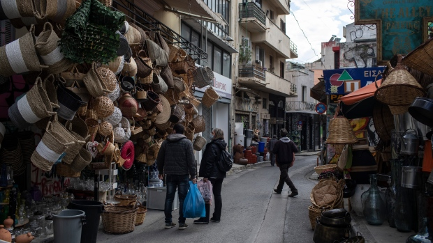 A man and a woman wearing protective face mask look at wicker items outside a shop in central Athens, Thursday, April 8, 2021.