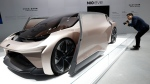 A visitor looks at the NIO eve concept car displayed during the Shanghai Auto Show, on April 19, 2021. (Ng Han Guan / AP)