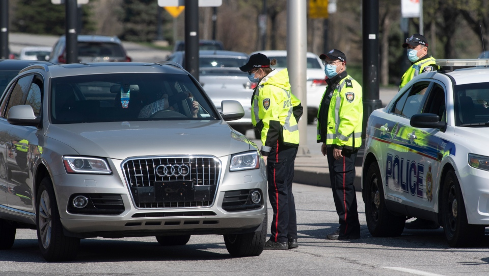 A driver shows identification to an Ottawa police officer as a checkpoint as vehicles enter the province from Quebec Monday April 19, 2021 in Ottawa. (Adrian Wyld/THE CANADIAN PRESS)