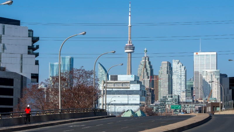 A runner passes by a lightly-travelled road in Toronto during rush hour on the first working day of the new Ontario COVID-19 lockdown on Monday, April 5, 2021. (Frank Gunn / THE CANADIAN PRESS)