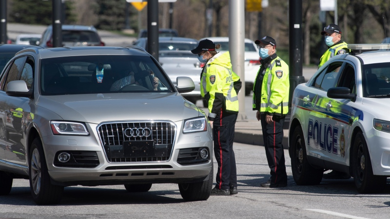 A driver shows identification to an Ottawa police officer as a checkpoint as vehicles enter the province from Quebec Monday April 19, 2021 in Ottawa. THE CANADIAN PRESS/Adrian Wyld