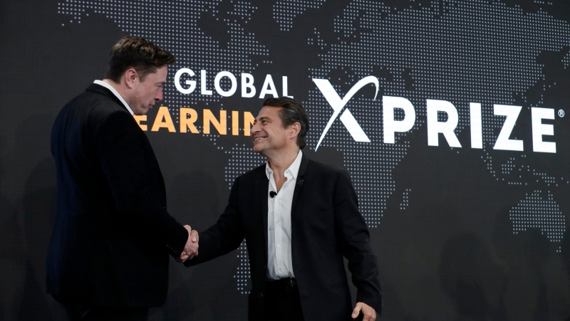 FILE - Tesla CEO Elon Musk, left, shakes hands with XPRIZE founder and Executive Chairman Peter Diamandis during the presentation of the XPRIZE for Children's Literacy in Los Angeles, in this Wednesday, May 15, 2019, file photo. (AP Photo/Marcio Jose Sanchez, File)