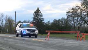 A police vehicle and barricades block the road where a 14-year-old boy died of his injuries after he was hit by a van while riding on a dirt bike in Ottawa's west end on April 18, 2021. (Aaron Reid/CTV News Ottawa)