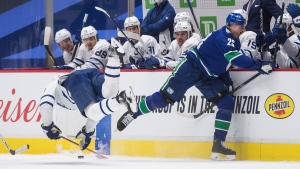 Vancouver Canucks' Alexander Edler, right, of Sweden, and Toronto Maple Leafs' Zach Hyman collide during the second period of an NHL hockey game in Vancouver, Sunday, April 18, 2021. (Darryl Dyck / THE CANADIAN PRESS)