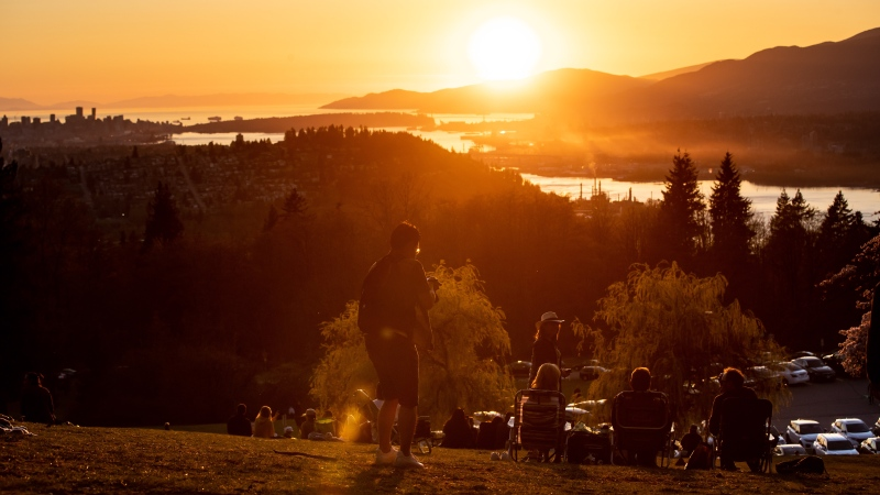 People watch the sunset over Vancouver from Burnaby Mountain Park, in Burnaby, B.C., on Saturday, April 17, 2021.