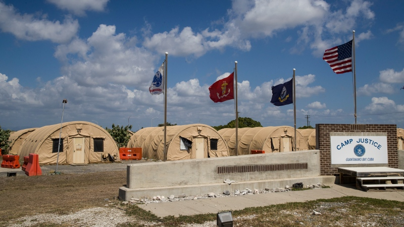In this April 18, 2019, file photo, in this photo reviewed by U.S. military officials, flags fly in front of the tents of Camp Justice in Guantanamo Bay Naval Base, Cuba. A plan to offer the COVID-19 vaccine to prisoners at the Guantanamo Bay detention center, which was halted earlier in 2021 amid a political backlash, is on again as health authorities on April 19, 2021 expanded the vaccination program on the Navy base in Cuba to the entire adult population of the remote facility (AP Photo/Alex Brandon, File)