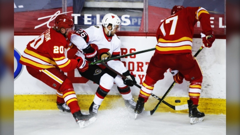 Ottawa Senators' Erik Brannstrom, centre, tries to get the puck away from Calgary Flames' Joakim Nordstrom, left, and Milan Lucic during third period NHL hockey action in Calgary, Alta., Monday, April 19, 2021. THE CANADIAN PRESS/Jeff McIntosh