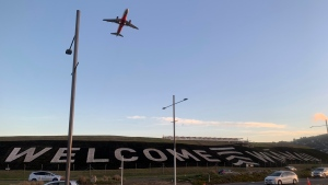 A giant sign painted near the main runway of the Wellington International Airport greets travelers returning home in Wellington, New Zealand Monday, April 19, 2021. (AP Photo/Nick Perry)