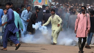 A supporters of Tehreek-e-Labiak Pakistan, a banned Islamist party, prepares to hurl back a tear gas canister fired by police to disperse protests over the arrest of their party leader Saad Rizvi, in Karachi, Pakistan, Monday, April 19, 2021. The outlawed Islamist political group freed 11 policemen almost a day after taking them hostage in the eastern city of Lahore amid violent clashes with security forces, the country's interior minister said Monday. (AP Photo/Fareed Khan)