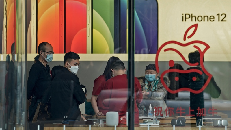 People wearing face masks to help curb the spread of the coronavirus look at iPad devices at an Apple store at the capital city's popular shopping mall in Beijing on Wednesday, Feb. 24, 2021. (AP Photo/Andy Wong)