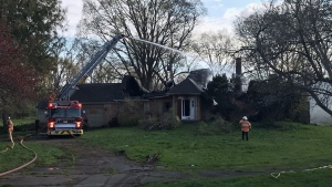 Crews spray water on hot spots following a fire at 1310 Adelaide St. North on Tuesday, April 20, 2021. (Sean Irvine / CTV London)