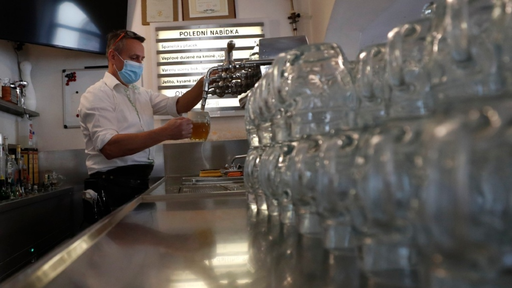 A bartender drafts a beer at a pub in Prague