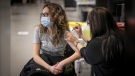 Nicole Fuerderer, 23, receives a COVID-19 vaccine from Nashrin Valani, Public Health Nurse, at the Telus Convention Centre in Calgary on April 19, 2021. (Leah Hennel/Alberta Health Services)