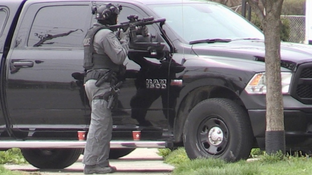 An armed officer stands in front of a property on Springbank Drive in London, Ont. on Tuesday, April 20, 2021. (Sean Irvine / CTV News)