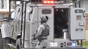 An armed police officer is seen on Springbank Drive in London, Ont. on Tuesday, April 20, 2021. (Sean Irvine / CTV News)