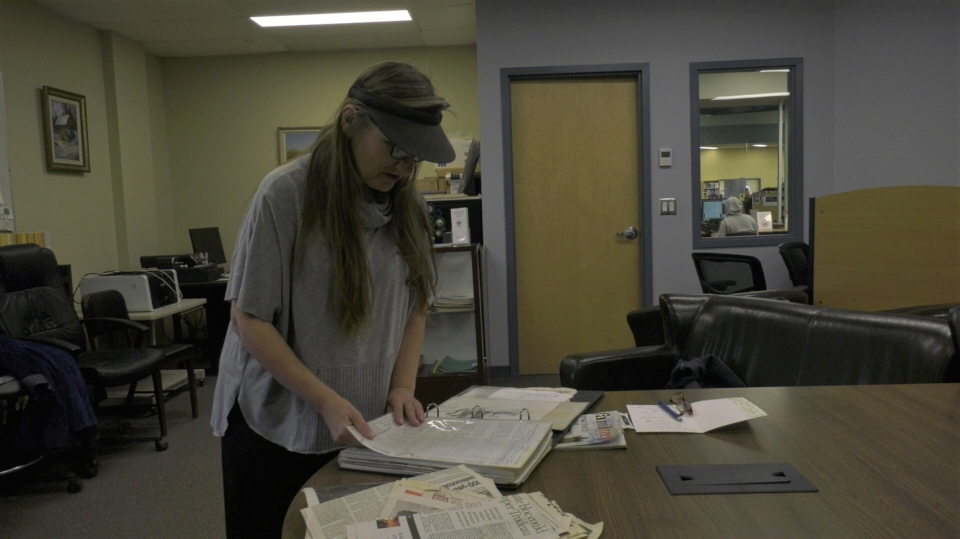 Lynda Burback goes through her father's old school records at Yorkton Public Library. (Kaylyn Whibbs/CTV Yorkton)