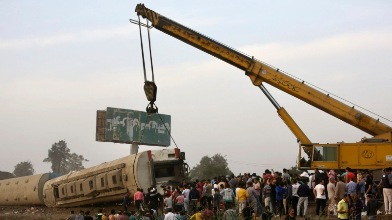 A crane is used to lift a part of a passenger train that derailed injuring some 100 people, near Banha, Qalyubia province, Egypt, Sunday, April 18, 2021. (AP Photo/Fadel Dawood)