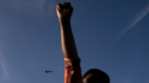 A Los Angeles Police helicopter hovers as Joyce Robertson, foreground, clenches her fist at the intersection of Florence and Normandie Avenues, Tuesday, April 20, 2021, in Los Angeles, after a guilty verdict was announced at the trial of former Minneapolis police Officer Derek Chauvin for the 2020 death of George Floyd. (AP Photo/Jae C. Hong)