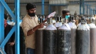 A worker checks oxygen cylinders before they are delivered to different hospitals at a gas supplier facility in Bengaluru, India, Wednesday, April 21, 2021. (AP Photo/Aijaz Rahi)