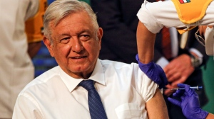 Mexican President Andres Manuel Lopez Obrador gets a shot of the AstraZeneca vaccine for COVID-19 during his daily, morning news conference at the presidential palace in Mexico City, Tuesday, April 20, 2021. (AP Photo/Fernando Llano)