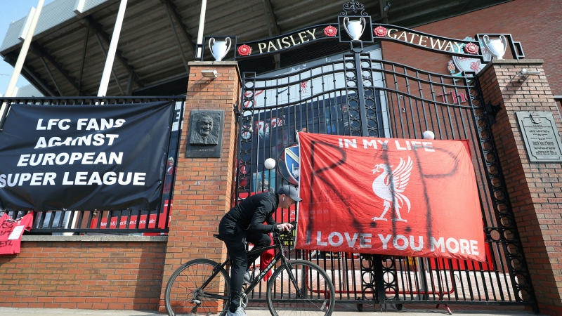 A man cycles past banners outside of Anfield Stadium, Liverpool, England protesting against the club's now-rescinded decision to join the European Super League, Tuesday April 20, 2021. After the aborted attempt to form a European Super League, Liverpool owner John Henry attempted to regain the trust of fans with an apology video on Wednesday. (Peter Byrne/PA via AP)