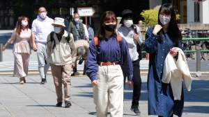 People wearing face masks to protect against the spread of the coronavirus visit Yasukuni Shrine in Tokyo, Wednesday, April 21, 2021, the first day of the annual Spring Rites, the Shinto shrine's biannual festival honoring the war dead. (AP Photo/Koji Sasahara)