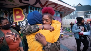 Maria Hamilton, mother of fatal police shooting victim Dontre Hamilton, embraces a supporter Tuesday, April 20, 2021, at a mural and memorial for George Floyd at the corner of N. Holton Street and E. North Avenue in Milwaukee. Former Minneapolis police Officer Derek Chauvin was found guilty on all counts in the murder of Floyd last May. Hamilton was killed April 30, 2014, after a Starbucks employee called the police on him for sleeping in Red Arrow Park. Hamilton, who suffered from schizophrenia, was shot 14 times by a Milwaukee police officer. The officer was fired for his actions leading up to the shooting, but not for his use of force. He was not prosecuted. (Mark Hoffman/Milwaukee Journal-Sentinel via AP)
