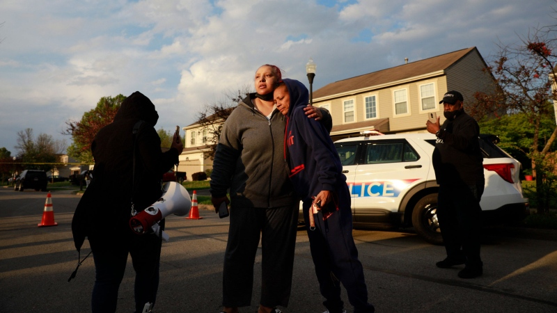 Hazel Washington is embraced after addressing a crowd with her anger at the Columbus Police at the shooting of her niece following a fatal police shooting on Tuesday, April 20, 2021 near Legion Lane on the east side of Columbus, Ohio. (Brooke LaValley/Columbus Dispatch via AP)